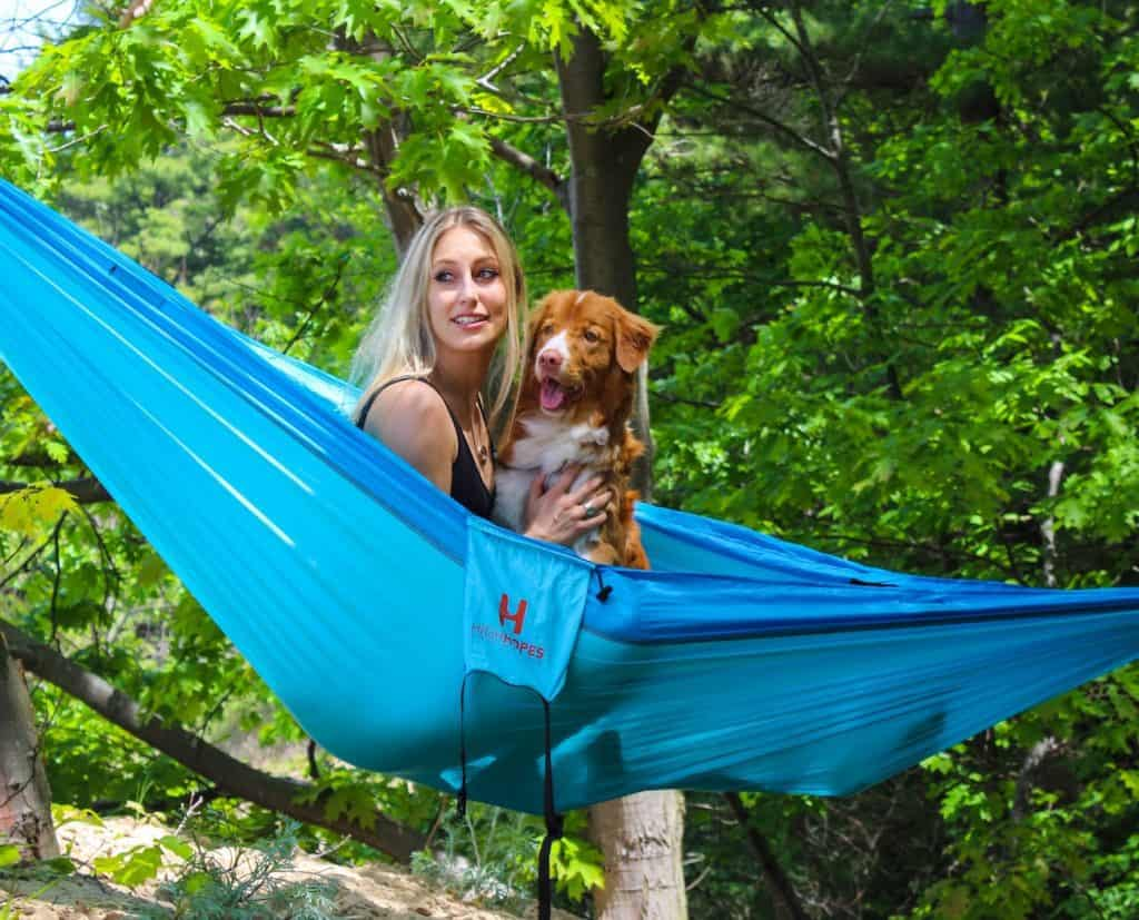 dog in hammock with blond woman owner