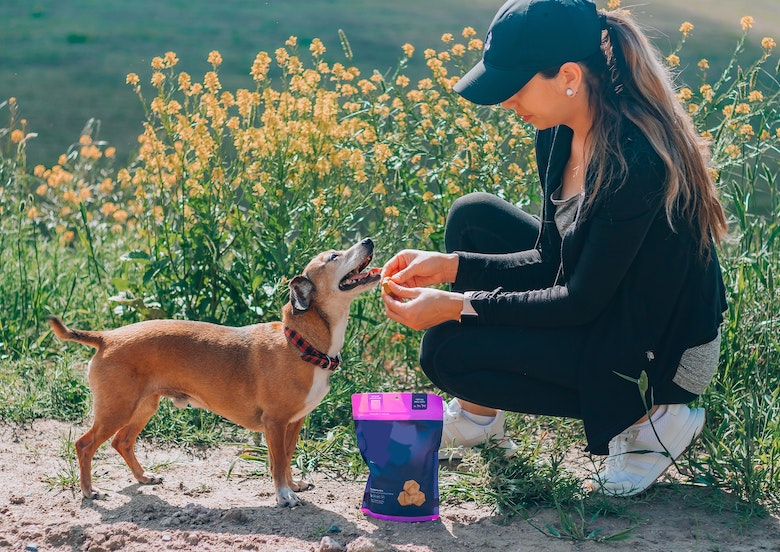woman giving dog treats on a trail