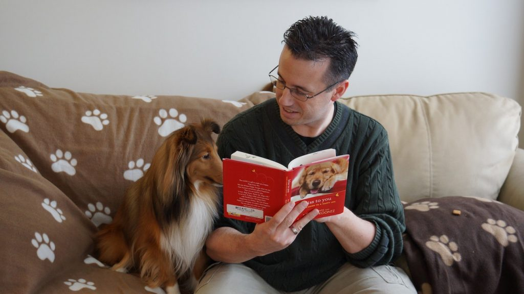 dog reading book with owner